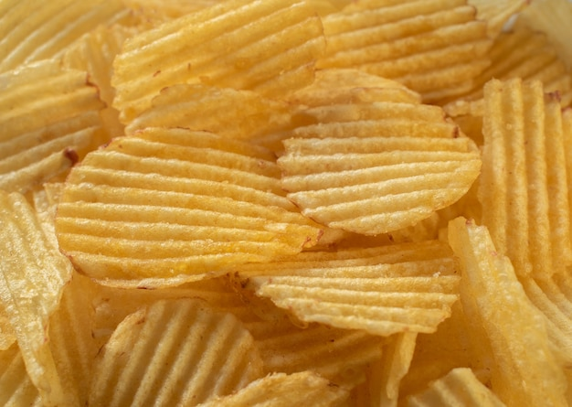 Kartoffelchips, die nahaufnahmetextur streuen