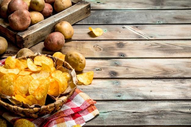 Kartoffelchips im korb auf rustikalem tisch.