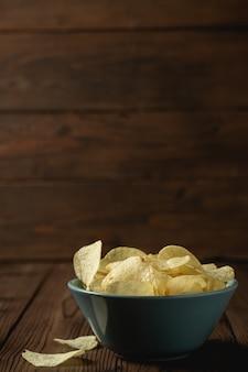 Kartoffelchips in der schüssel auf einem holztisch.