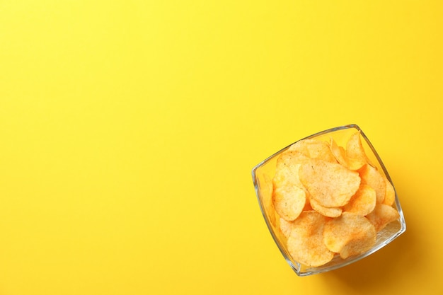 Kartoffelchips in einem teller. biersnacks auf gelb, platz für text. draufsicht