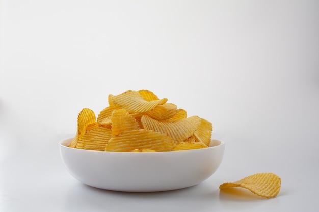 Kartoffelchips in einem weißen teller auf weißem hintergrund.