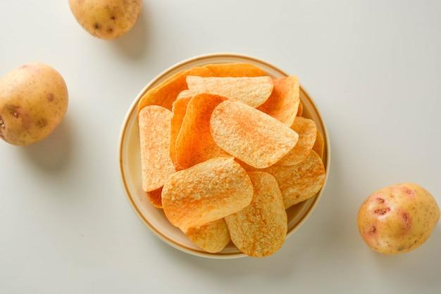 Kartoffelchips in einer platte lokalisiert auf einem weißen hintergrund