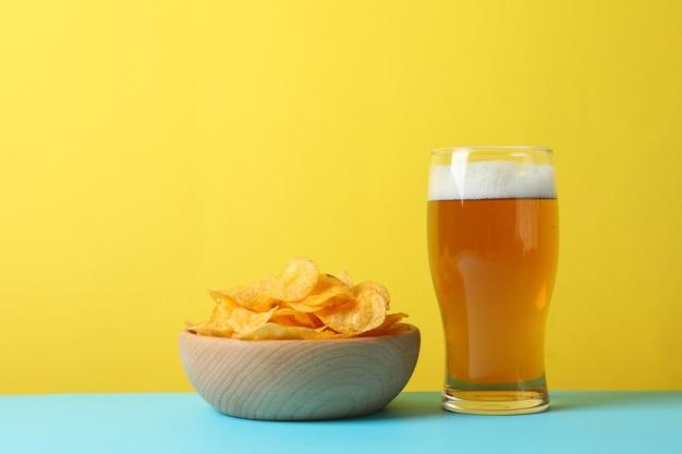 Kartoffelchips in einer schüssel und einem glas bier. bier snacks auf blau gegen gelb, platz für text