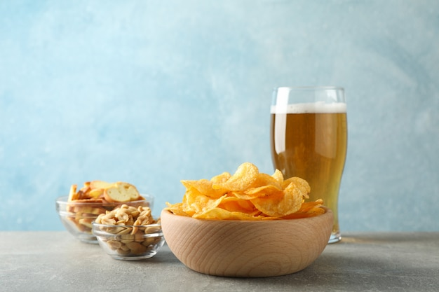 Kartoffelchips in einer schüssel und einem glas bier. biersnacks, biernüsse auf grauem tisch auf blau, platz für text