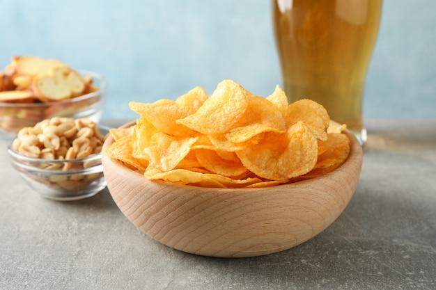 Kartoffelchips in einer schüssel und einem glas bier. biersnacks, biernüsse auf grauem tisch gegen blau, platz für text. nahansicht