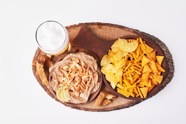 Kartoffelchips mit bier auf weiß.