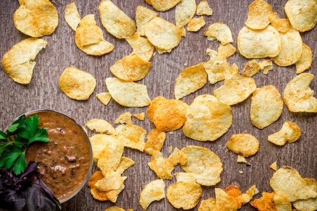 Kartoffelchips mit dip auf einem holztisch ungesundes essen auf holzhintergrund