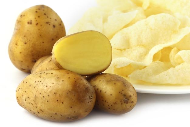 Kartoffelchips mit frischen kartoffeln auf weißem hintergrund