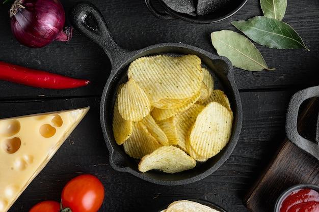 Kartoffelchips mit käse und zwiebeln, auf schwarzem holztisch, draufsicht flach gelegt
