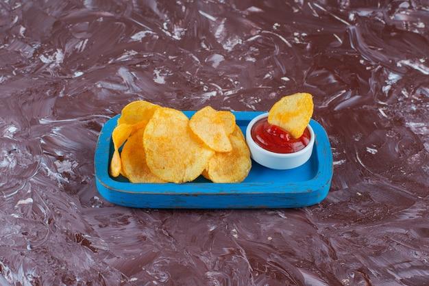 Kartoffelchips mit ketchup in einer holzplatte auf dem marmortisch.