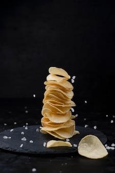 Kartoffelchips und salz in der zusammensetzung auf schwarzem hintergrund.
