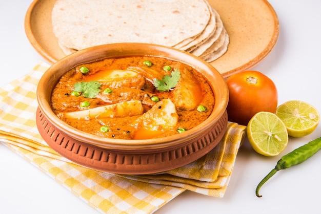 Kartoffelcurry oder aaloo oder aaloo masala fry mit grünen erbsen, indisches hauptgericht, serviert mit fladenbrot, auch bekannt als chapati oder roti, selektiver fokus