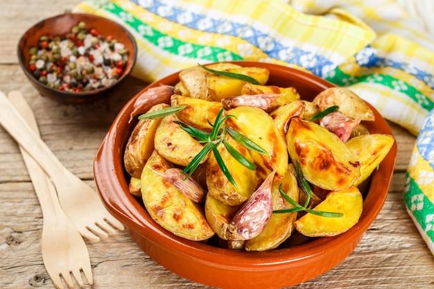 Kartoffelecken mit knoblauch, rosmarin und gewürzen überbacken
