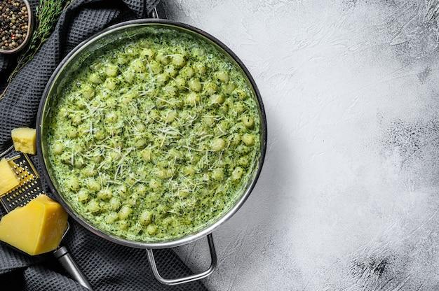 Kartoffelgnocchi mit pesto, parmesan und spinat. italienische pasta. grauer hintergrund. draufsicht. speicherplatz kopieren