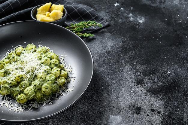 Kartoffelgnocchi mit pesto, parmesan und spinat. italienische pasta. schwarzer hintergrund