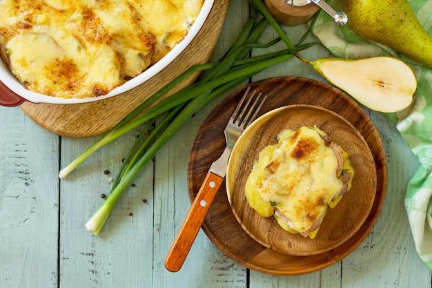 Kartoffelgratin mit birnen-raclette-käse und speck auf rustikalem holztisch ansicht von oben