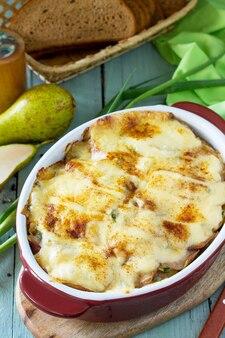 Kartoffelgratin mit birnen-raclette-käse und speck auf rustikalem holztisch