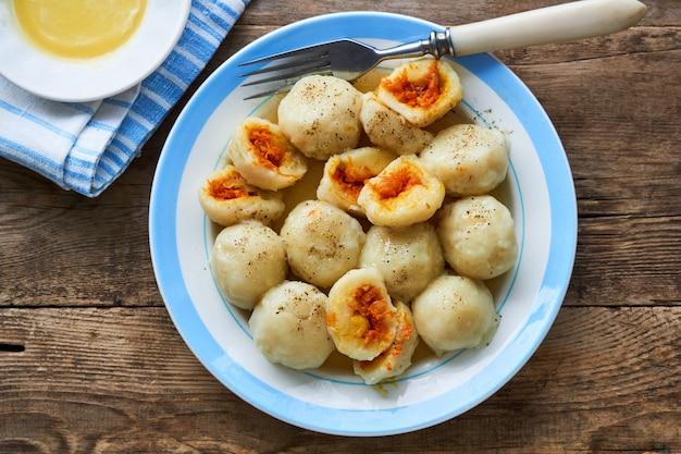Kartoffelknödel gefüllt mit karotten auf einem teller