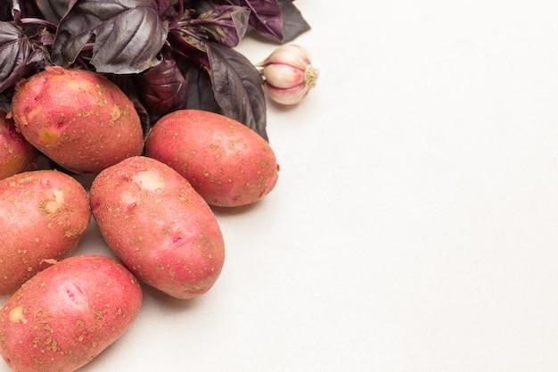 Kartoffelknollen, knoblauch und blaues basilikum. platz kopieren. weißer hintergrund