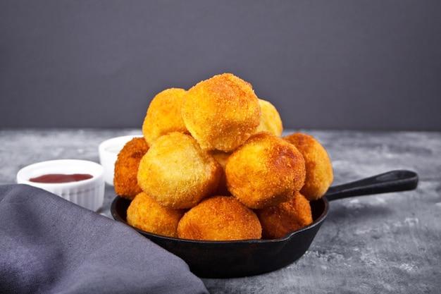 Kartoffelkrokettenbällchen auf der eisenpfanne und dip-saucen.
