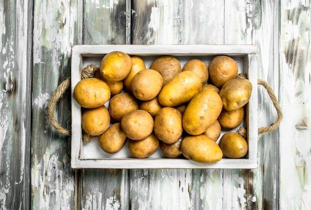 Kartoffeln auf dem tablett. auf weißem hölzernem hintergrund