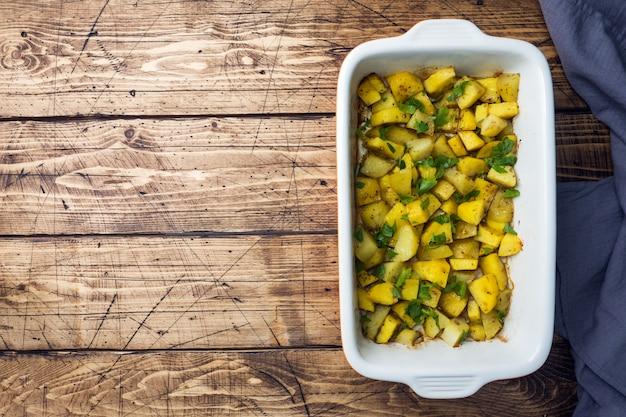 Kartoffeln gebacken mit gewürzen und kräutern in einem keramischen backblech. vegetarische küche platz kopieren