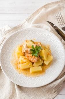 Kartoffeln gedämpft mit huhn und gemüse auf einer platte.