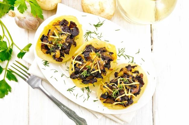 Kartoffeln gefüllt mit pilzen, gebratenen zwiebeln und käse in einem teller auf serviette, pflanzenöl in dekanter, petersilie, knoblauch und einer gabel auf dem hintergrund eines hellen holzbretts von oben