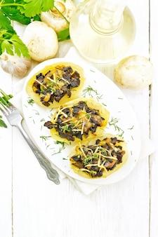 Kartoffeln gefüllt mit pilzen, gebratenen zwiebeln und käse in einem teller auf serviette, pflanzenöl in dekanter, petersilie, knoblauch und einer gabel auf holzbretthintergrund von oben