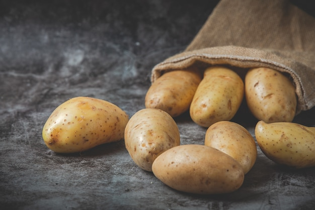 Kartoffeln gießen aus säcken auf grauem boden