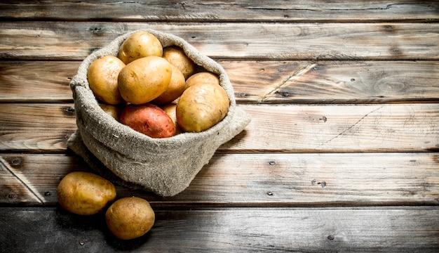 Kartoffeln im sack. auf hölzernem hintergrund