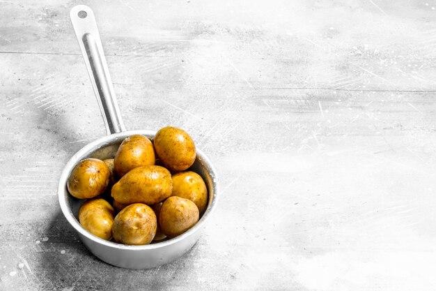 Kartoffeln in der kelle. auf weißem rustikalem hintergrund