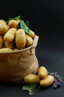 Kartoffeln in einem gemusterten sack mit lila blüten und seitenansicht der blätter
