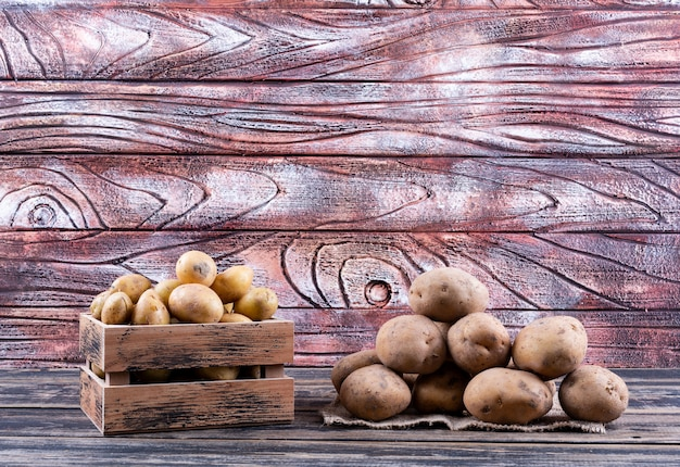 Kartoffeln in einer holzkiste und auf sackbeutel-seitenansicht auf einem holztisch
