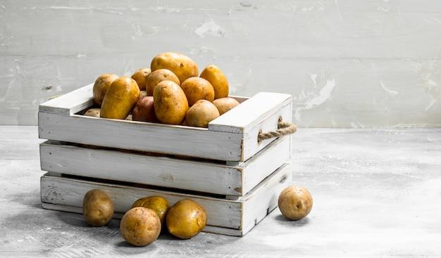 Kartoffeln in einer schachtel. auf weißem rustikalem hintergrund
