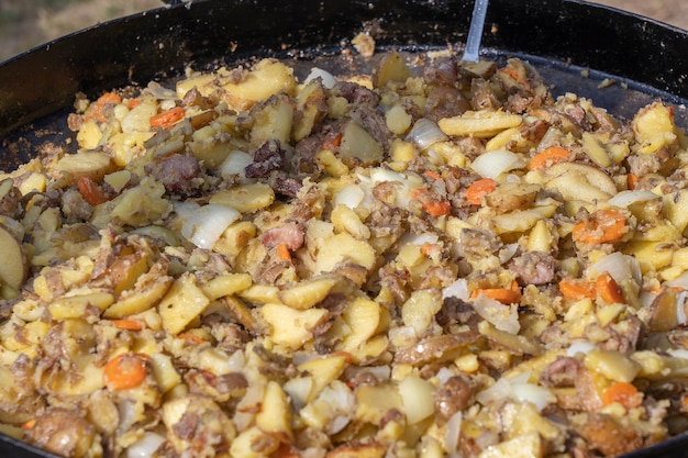 Kartoffeln, karotten, zwiebeln und fleisch in einer großen pfanne anbraten. leckeres essen auf dem festival. feldküche am herd. junge kartoffeln werden in öl gebraten, streetfood, ukraine