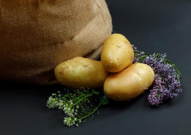 Kartoffeln mit lila blumen und stoffsack