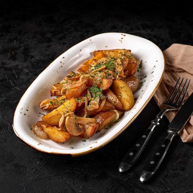 Kartoffeln nach art des hauses. bratkartoffeln mit zwiebeln, knoblauch und champignons.