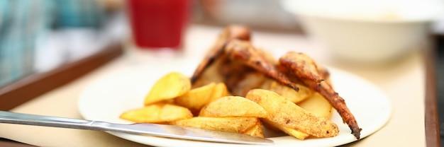 Kartoffeln und gegrillte hühnerflügel auf teller.