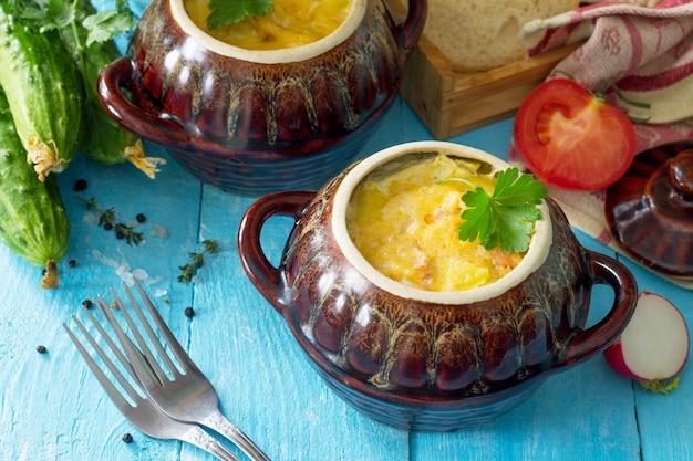 Kartoffeln und roter fisch mit sahne und käse backen in tontöpfen im hölzernen hintergrund der küche