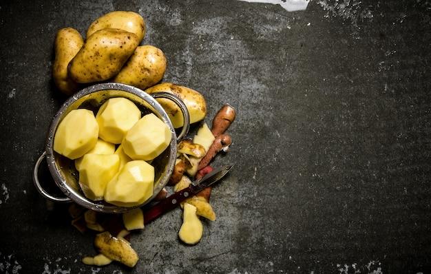 Kartoffelnahrung. das konzept der nassen geschälten kartoffeln auf einem steinhintergrund. freier platz für text. draufsicht