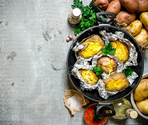 Kartoffelnahrung. das konzept der ofenkartoffel in folie auf einem alten rustikalen tisch. freier platz für text. draufsicht