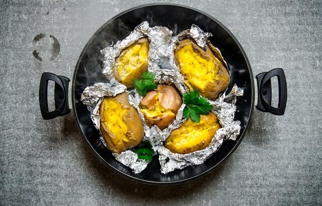Kartoffelnahrung. ofenkartoffeln in einer pfanne auf einem alten rustikalen tisch. draufsicht