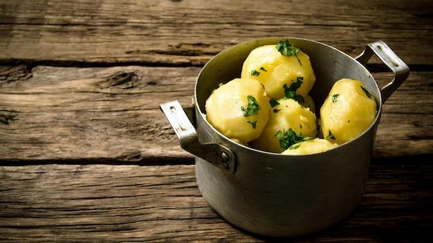 Kartoffelnahrung. salzkartoffeln mit kräutern auf holztisch. freier platz für text.