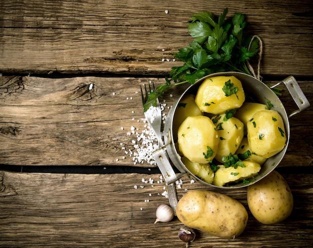 Kartoffelnahrung. salzkartoffeln mit kräutern und salz auf einem holztisch. freier platz für text. draufsicht