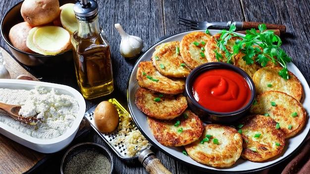 Kartoffelpfannkuchen mit hüttenkäse mit knoblauch, petersilie, serviert mit ketchup auf einem teller auf holzuntergrund, draufsicht, nahaufnahme close