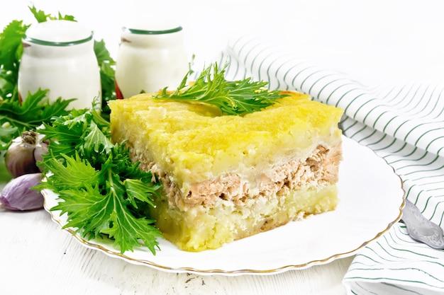 Kartoffelpüree-auflauf mit lachsfilet und salat in einem teller, küchentuch, knoblauch auf dem hintergrund eines hellen holzbretts