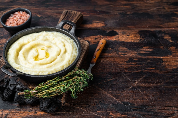 Kartoffelpüree in einer pfanne auf rustikalem holztisch