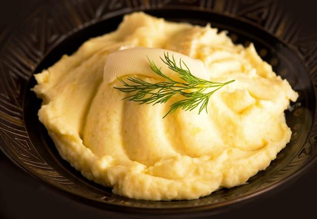 Kartoffelpüree in schüssel auf holztisch.