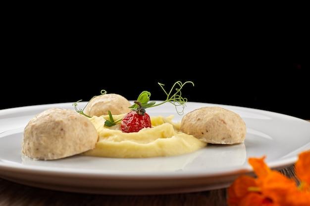 Kartoffelpüree mit dampffleischbällchen auf einem weißen teller